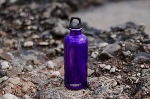 Purple water bottle surrounded by rocks