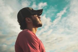 Man under blue sky breathing