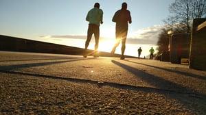 Two men running in sunshine